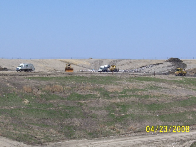 Landfill Working Area with garbage trucks and compactors